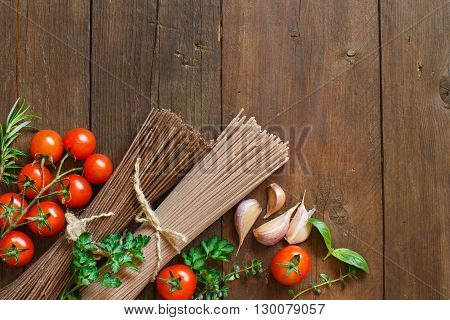 Three types of spaghetti tomatoes and herbs on wood
