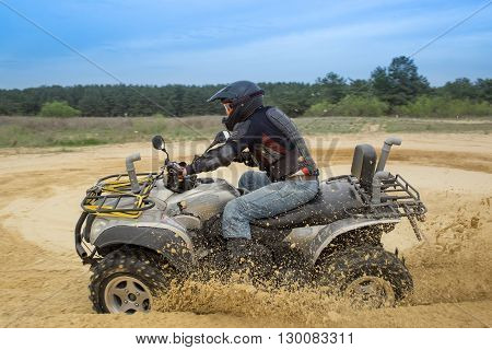 Racing ATV in the sand in the summer on the prepared track.