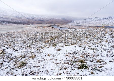 Scenic landscape with field mountain snow and dramatic sky in winter of Iceland