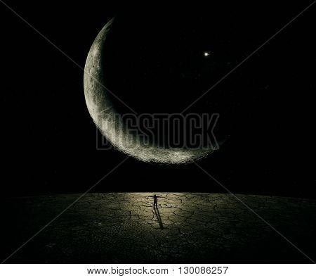 Man standing in front of a giant new moon with hands wide opened. Courage freedom power concept