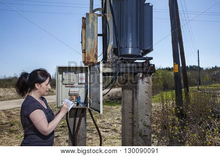 Electrician engineer woman checking electricity meter and invoice standing near electricity switchgear power transformer substation outdoors.