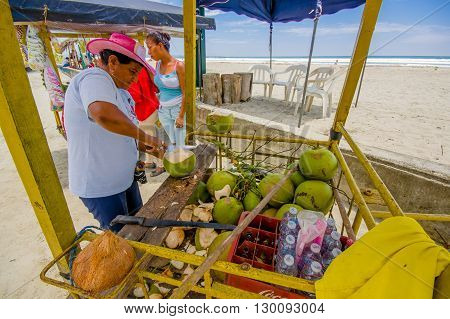 Muisne, Ecuador - March 16, 2016: Local street vendor working and using knife on green coconuts, beachside pacific ocean.