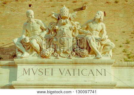 VATICAN, ITALY - JUNE 13, 2015: Wall signboard to enter to Vatican Museums, sculture with Vatican seal on stone.
