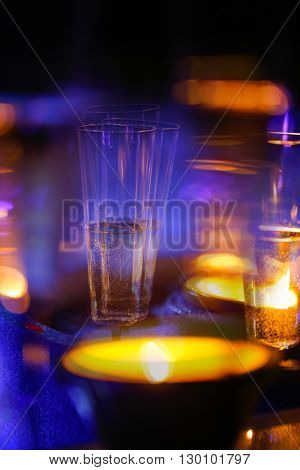 Blurred candlelit champagne glasses. Alcoholism intoxication double vision drunkenness high class party debauchery concept.