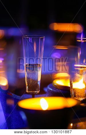 Extravagant private romantic candlelit champagne glasses with a jacuzzi in the background. Love celebration relax romance luxurious vacation wellness spa concept.
