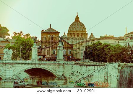 VATICAN, ITALY - JUNE 13, 2015: Far view to Saint Peter dome at Vatican, graffittis under the breach and sunset light.