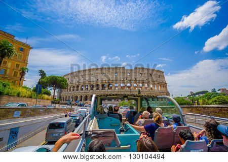 ROME, ITALY - JUNE 13, 2015: Turists bus visiting the most important places in Rome city, people watching from their seats. Roman Coliseum
