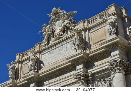 Beautiful attic of Trevi Fountain with Pope emblem among angels and allegoric statues