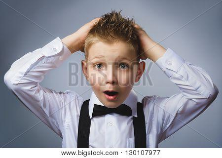 Closeup portrait headshot nervous anxious stressed afraid boy isolated grey background. Negative emotion facial expression.