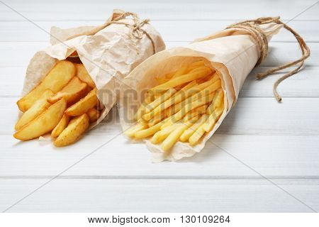 Potato wedges and french fries wrapped in brown wrapping paper. Fast food take away at white shabby chic wood. Fried potatoes with tomato sauce. Chips, potato slices. Top view, flat lay, closeup.
