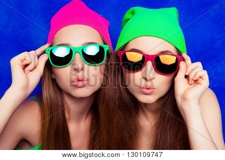 Portrait Of Two Pretty Sisters In Hats And Glasses Pouting
