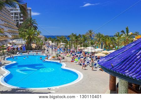 TAURITO, GRAN CANARIA, SPAIN - APRIL 20, 2016: Tourists on sun holidays at the pool of Paradise Lago Taurito hotel, Gran Canaria. Paradise is a complex of 4 hotels in Gran Canaria.