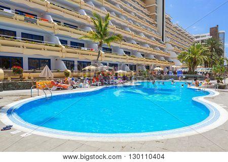 TAURITO, GRAN CANARIA, SPAIN - APRIL 20, 2016: Tourists on sun holidays at the pool of Paradise Lago Taurito hotel, Gran Canaria. Paradise is a complex of 4 hotels in Gran Canaria.
