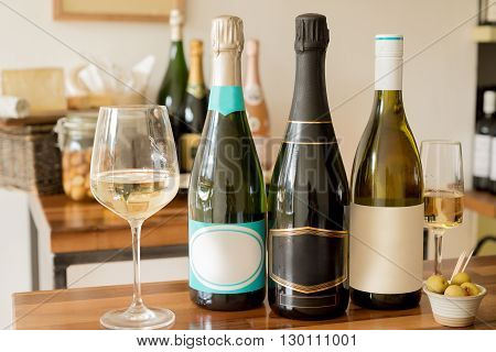 Bottles of unopened champagne or sparkling wine with blank labels between wineglasses and a tiny bowl of olives