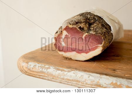 A roll of ham or cured meat on a wooden counter
