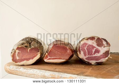 Three deli meat or lunch meat logs on a wooden counter