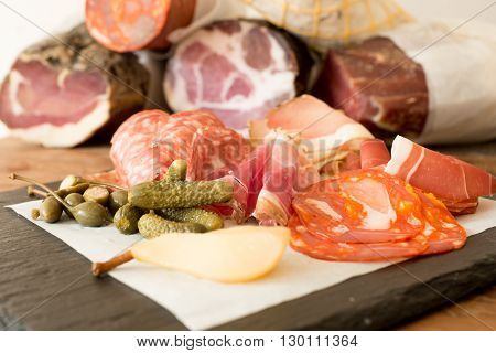 A variety of sliced lunch meat alongside fruits and pickled cucumbers on a slate with deli meat logs in the background