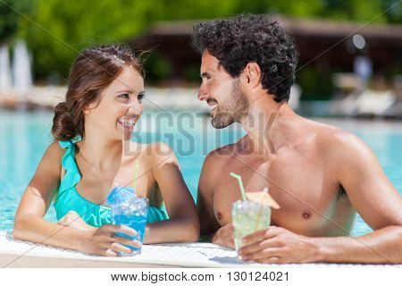 Young couple having a drink in a swimming pool