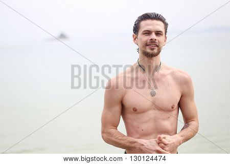 The young handsome man against the sea. The guy smiles and looks forward.