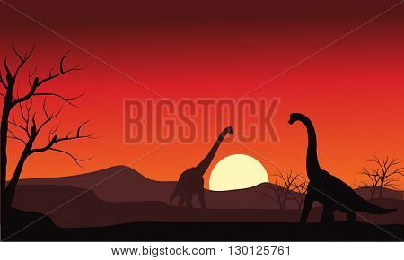 Silhouette of two brachiosaurus at sunset with sun