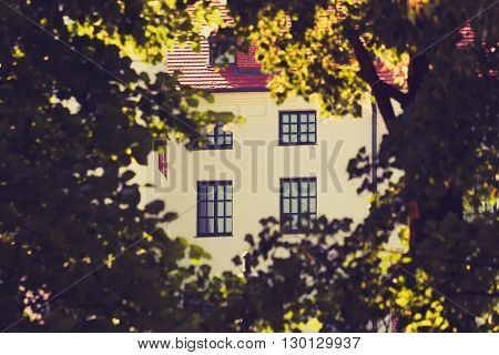 View to light facade of building with windows through the bushy foliage of trees in sunny day. Tinted image