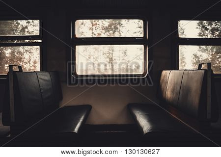 Inside view of empty passenger seats near the light window. Tinted image
