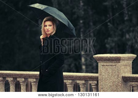 Sad young fashion woman with umbrella walking in the rain