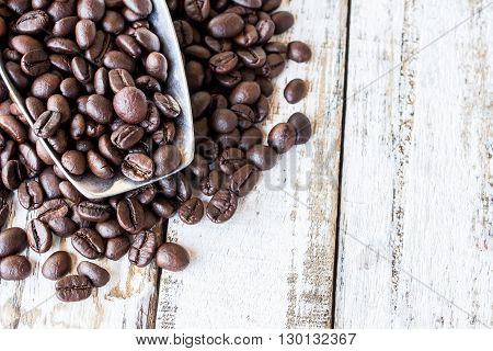 Big stainless steel scoop of coffee beans on white wooden table
