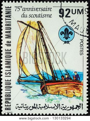 MOSCOW RUSSIA - MAY 14 2016: A stamp printed in Mauritania shows sailing boat with scouts series