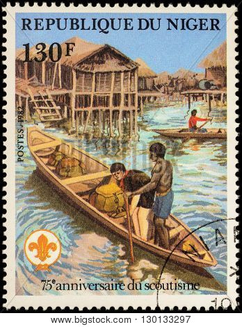 MOSCOW RUSSIA - MAY 14 2016: A stamp printed in Niger shows boyscout in canoe with backpacks in Aboriginal village series