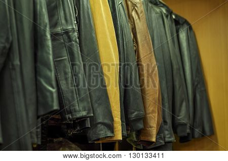 Hanging leather jackets on clothes rack in leather shop. Finished beautiful leater jackets are hanging and ready for shipping or selling in a leather workshop. The leather jackets are in sharp focus, but no human face or figure is not visible.