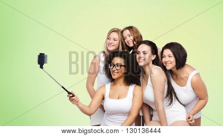 technology, friendship, body positive and people concept - group of happy women in white underwear taking picture with smartphoone on selfie stick over green natural background