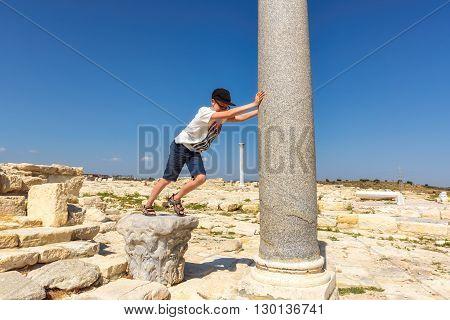 Cyprus Landmark. Teenager sustains a falling column in old greek ruins city of Kourion near Limassol