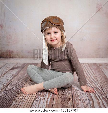 cute little girl in airman hat sitting on wooden floor