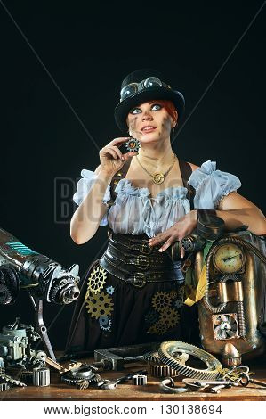 Steam-punk portrait of the girl with the mechanisms on a dark background