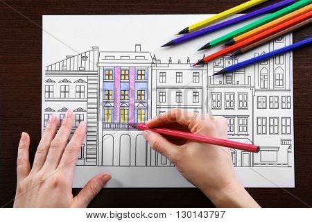 Female hand drawing with soft tip pencil in adult anti stress coloring closeup