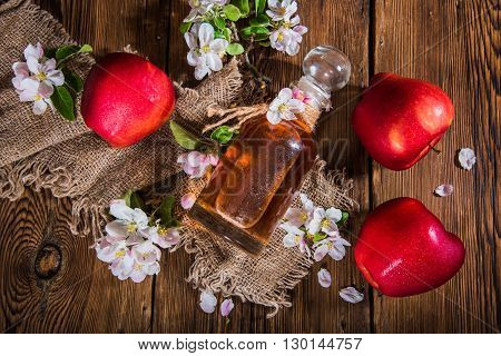 A bottle of apple cider vinegar (cider), fresh apples and apple-tree flowers on a wooden background. Country style.
