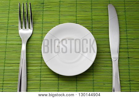 Small plate for diet next to a knife and fork on green bamboo placemats