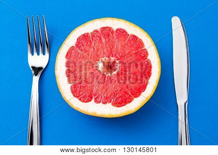 Fresh ripe grapefruit is lying between fork and knife symbolizing a healthy eating. Fruit still life