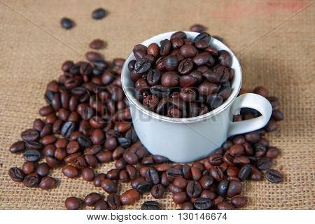Dark roasted coffee beans in white cup with along with some coffee beans and gunny sack texture on background