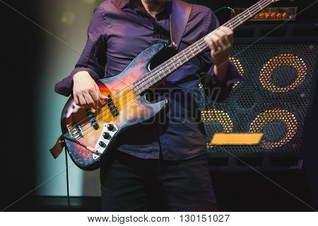 Bass Guitar Player On A Stage Near Speakers