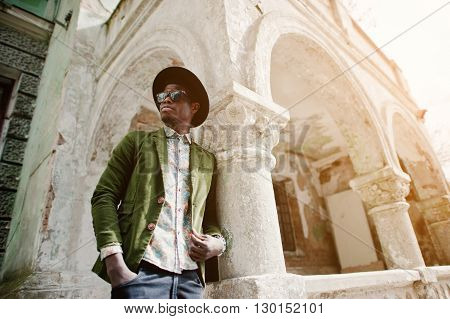 Fashion Portrait Of Black African American Man On Green Velvet Jacket And Black Hat, Leaned At Colum