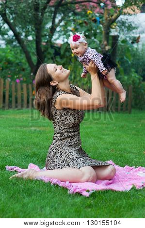 child and parenthood concept - happy mother with little baby sitting on blanket in park.