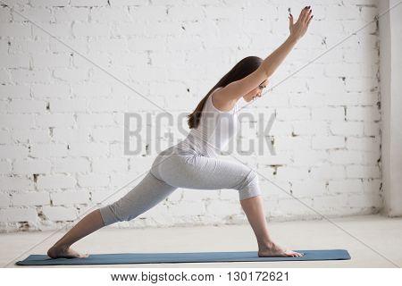 Profile Portrait Of Beautiful Woman Doing Warrior I Pose