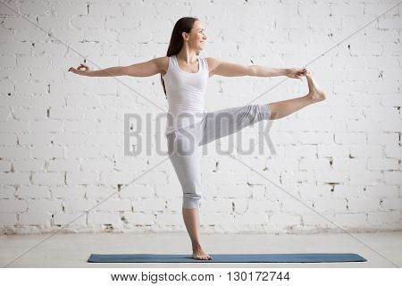 Side View Portrait Of Happy Woman Doing Extended Hand To Big Toe Pose