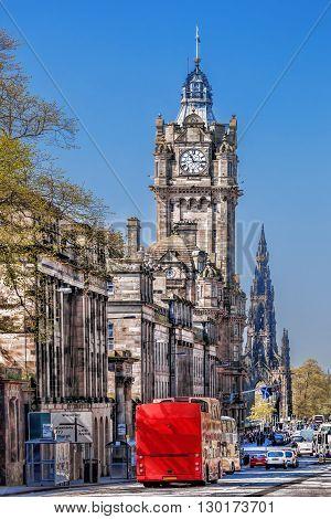 Edinburgh With Red Bus Against Clocktower In Scotland, Uk