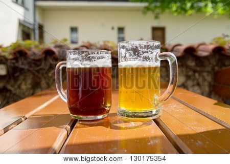 two mugs of beer on a table at an outdoor cafe