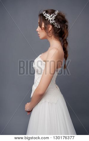 Bridal fashion. Brunette bride in wedding dress and beaded headpiece.