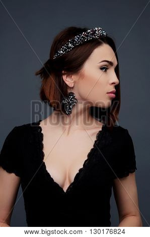 Sexy brunette in black dress with deep cleavage wearing beaded crown headpiece and earrings