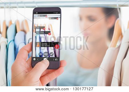 Female hand holding a smartphone against digital image of shopping online